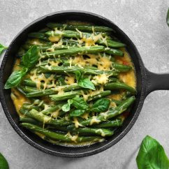 Frying pan with delicious green bean casserole on kitchen table